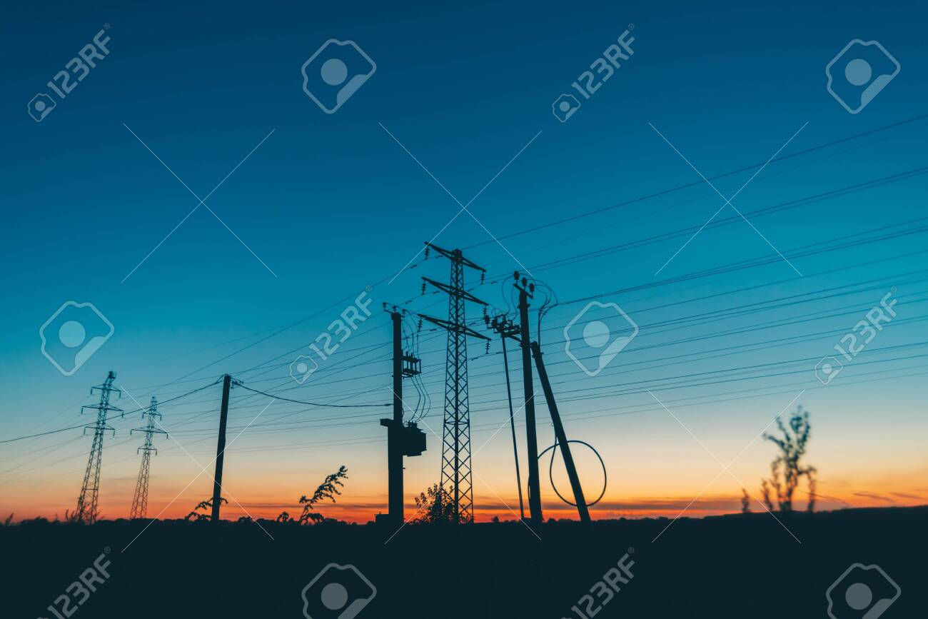 Power lines in field on sunrise background. Silhouettes of poles with wires at dawn. Cables of high voltage on warm orange blue sky. Power industry at sunset. Many cables in picturesque vivid sky. - 120653433