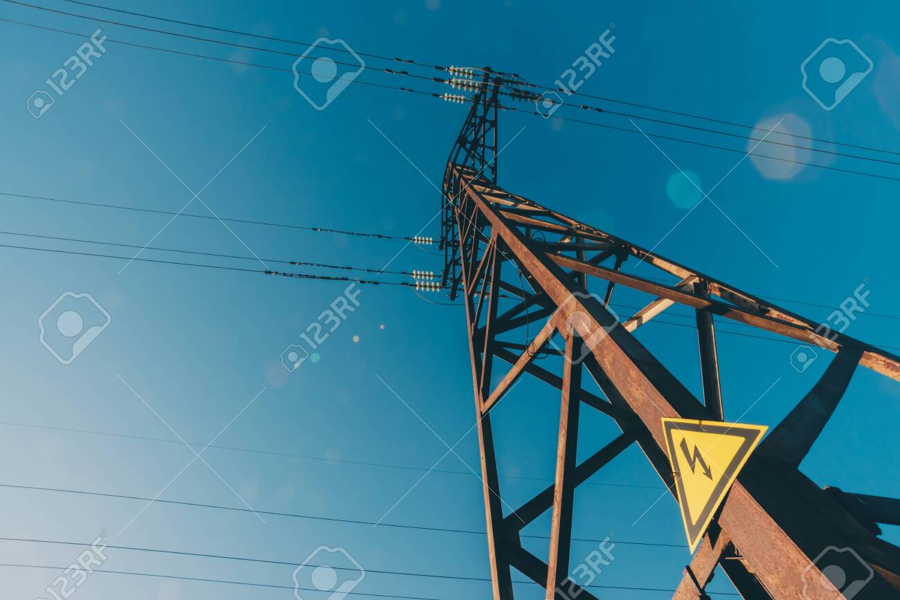 Power lines on background of blue sky close-up. Electric hub on pole. Electricity equipment with copy space. Wires of high voltage in sky. Electricity industry. Tower with lightning warning sign. - 120799329