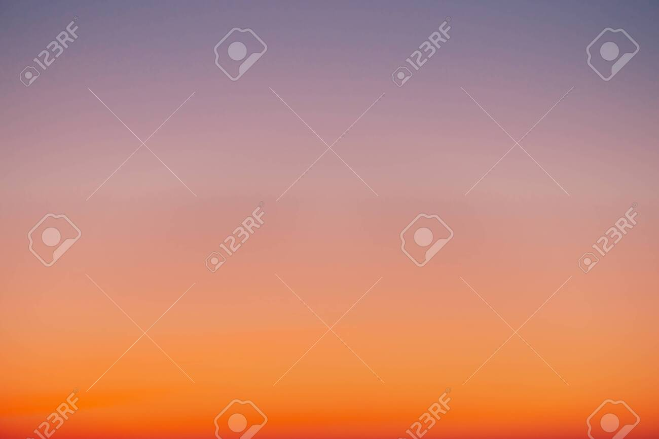 Predawn clear sky with orange horizon and violet atmosphere. Smooth orange violet gradient of dawn sky. Background of day beginning. Heaven at early morning with copy space. Sunset, sunrise backdrop - 122210030