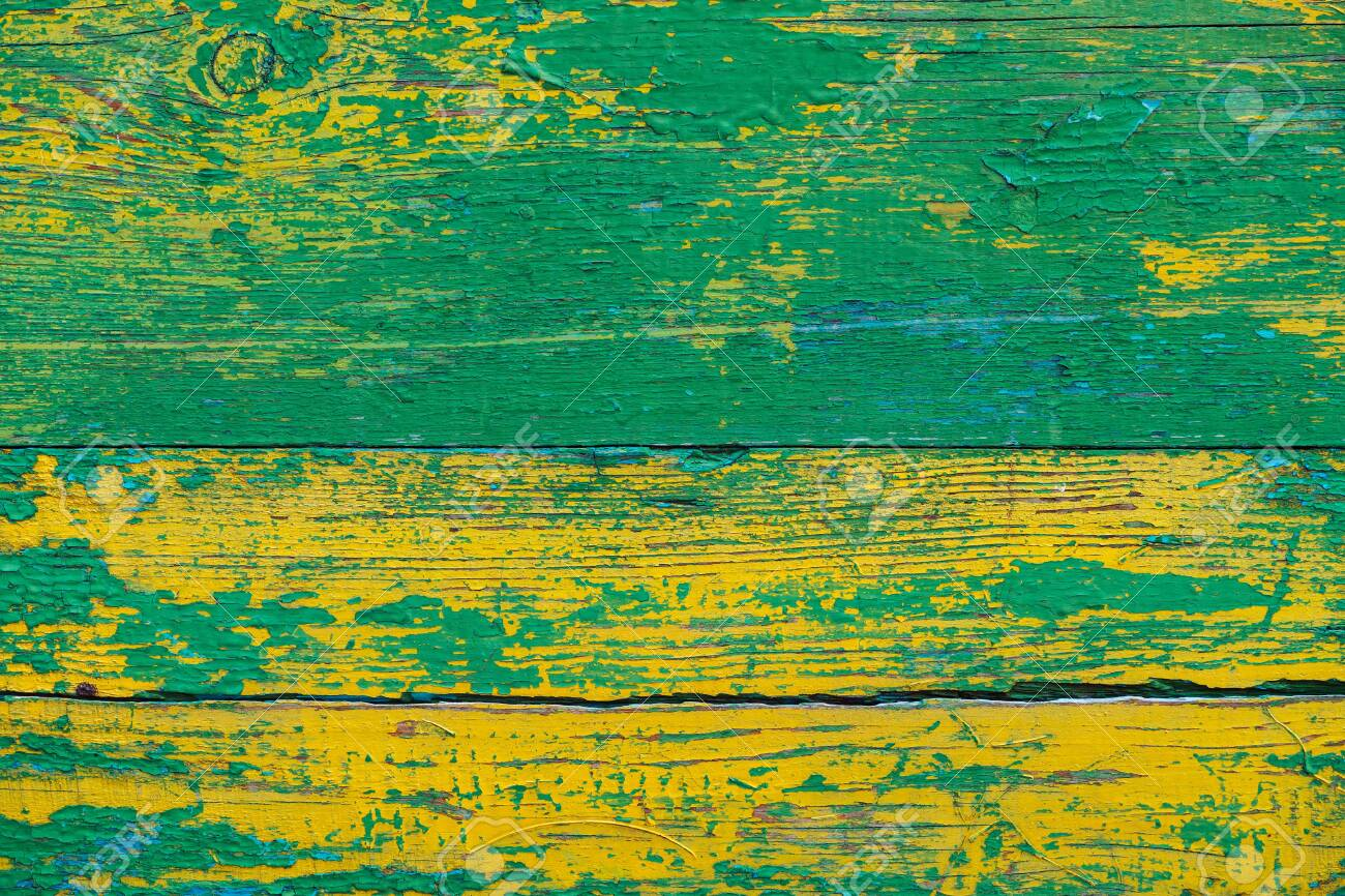 Old wooden painted rustic wall with yellow green flaky dye  Faded