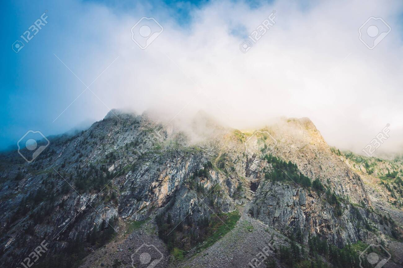 Giant cloud above rocky ridge with trees in sunlight. Amazing mountain range under blue cloudy dawn sky. Wonderful foggy rocks. Misty landscape of highland nature. Low clouds in morning sunny light. - 122474920