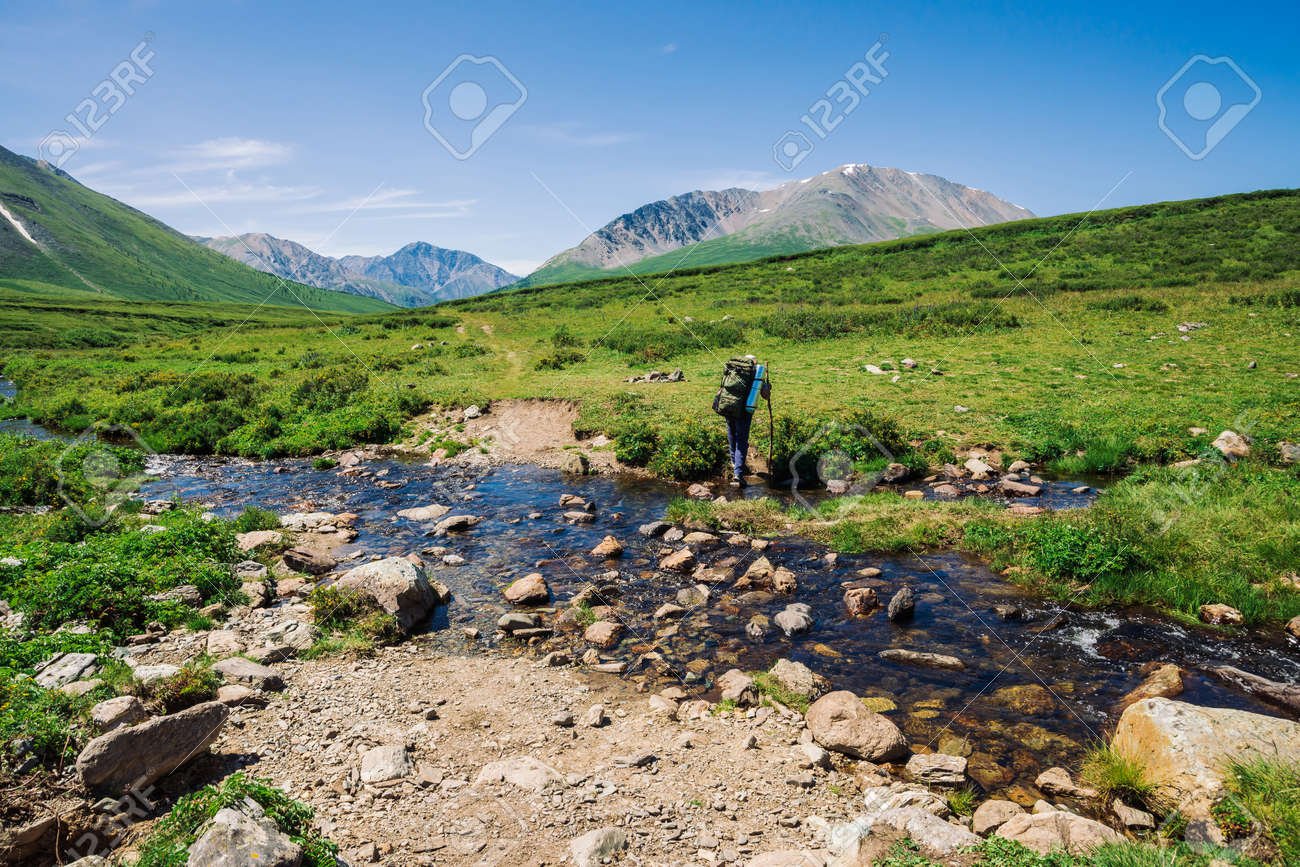 Man with large backpack crosses mountain creek over stones. Tourist goes on path in green valley to wonderful snowy mountains. Hiking in highlands. Amazing atmospheric landscape of majestic nature. - 122478620