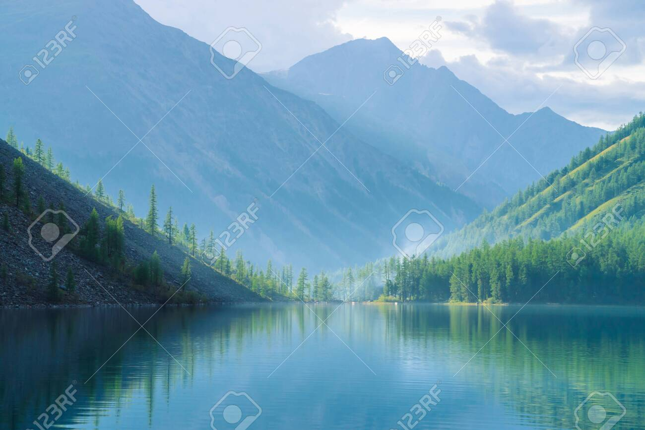 Ghostly mountain lake in highlands at early morning. Beautiful misty mountains reflected in calm clear water surface. Smoke of campfires. Amazing atmospheric foggy landscape of majestic nature. - 122547472