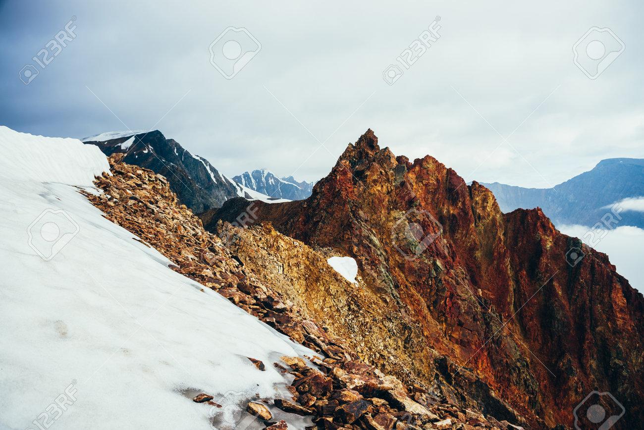 Beautiful pointed rocky pinnacle on giant snowy mountain. Vivid big pointy rocky peak. Atmospheric minimalist alpine landscape. Sharp rocky mountain top in cloudy sky. Wonderful highland scenery. - 166450430