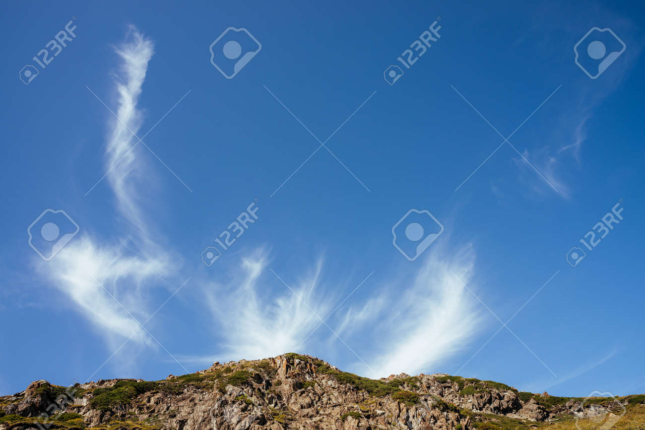 Scenic mountain landscape with beautiful cirrus clouds in clear blue sky over rocks in sunlight. Colorful highland scenery with spindrift clouds in blue clear sky above green brown rocky mountains. - 170160614