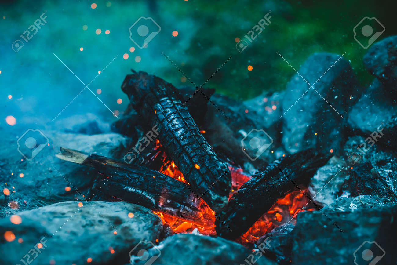 Vivid smoldered firewoods burned in fire closeup. Atmospheric background with orange flame of campfire. Full frame image of bonfire with sparks in bokeh. Warm vortex of glowing embers and ashes in air - 170494546
