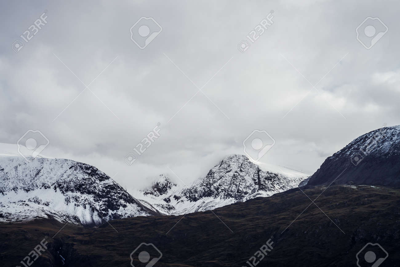 Great black mountains with white snow on tops and glaciers. Dramatic landscape with snowy mountains under cloudy gray sky. Atmospheric alpine scenery with snow on rocky mountains in overcast weather. - 170494513