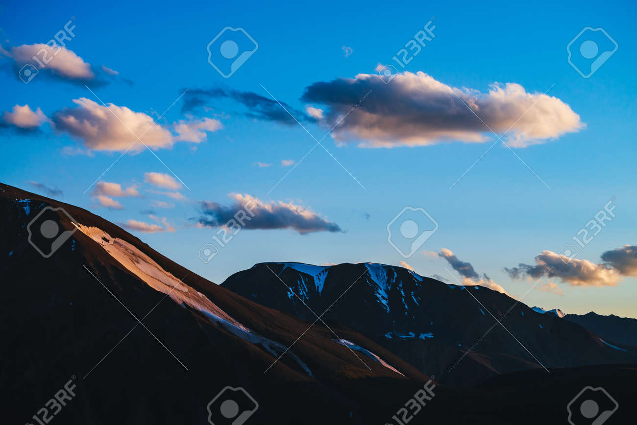 Atmospheric dawn landscape with silhouettes of snowy mountains with glaciers. Sunset sky with golden fluffy clouds. Colorful mountain scenery with golden snow on sunrise. Scenic view to mountains. - 170495038