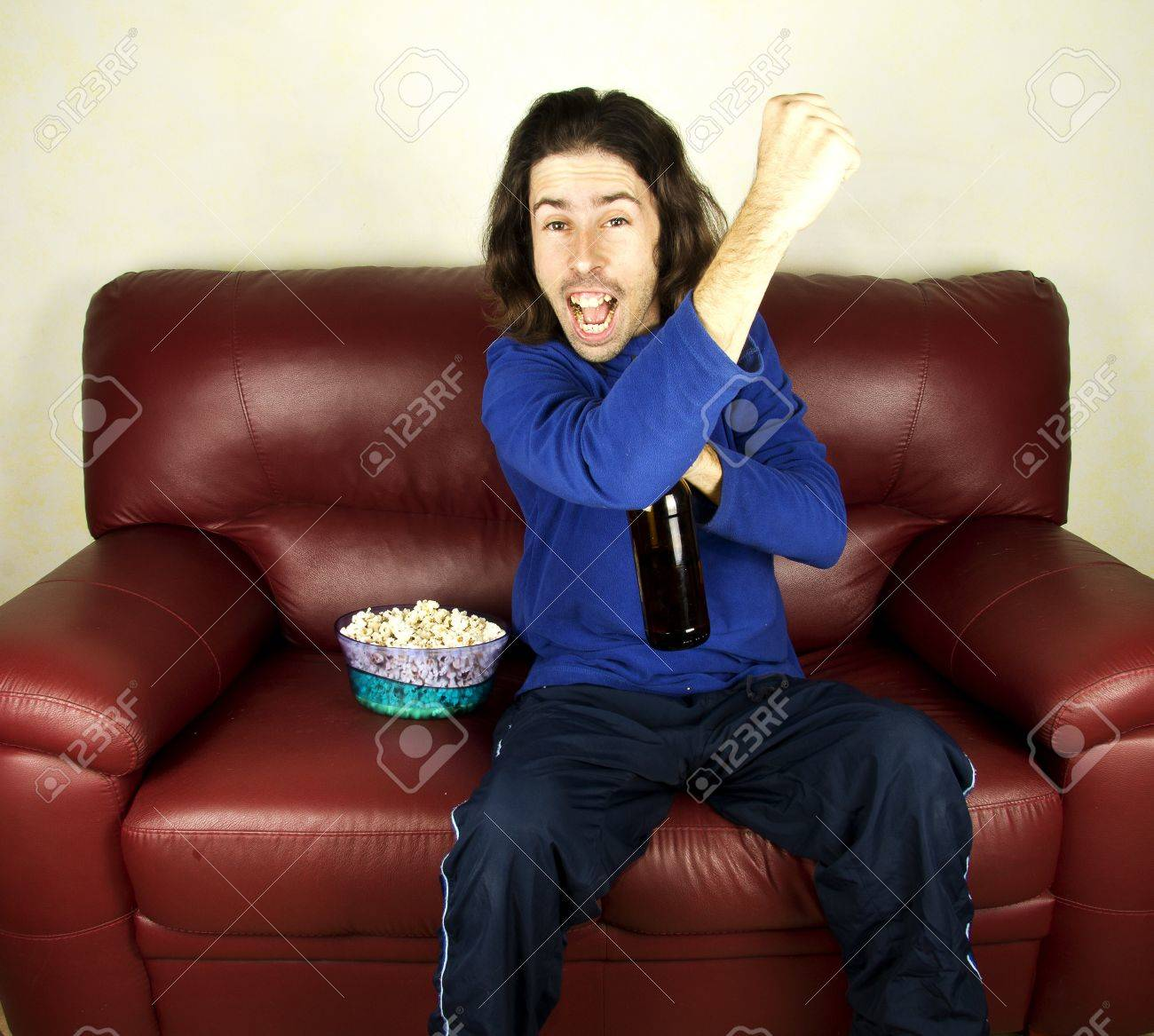 a young man look the football on the couch Stock Photo - 17603685
