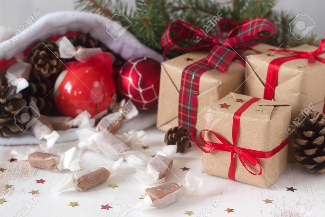 Gifts and homemade toffee in Christmas decorations. Rustic style, selective focus. Stock Photo