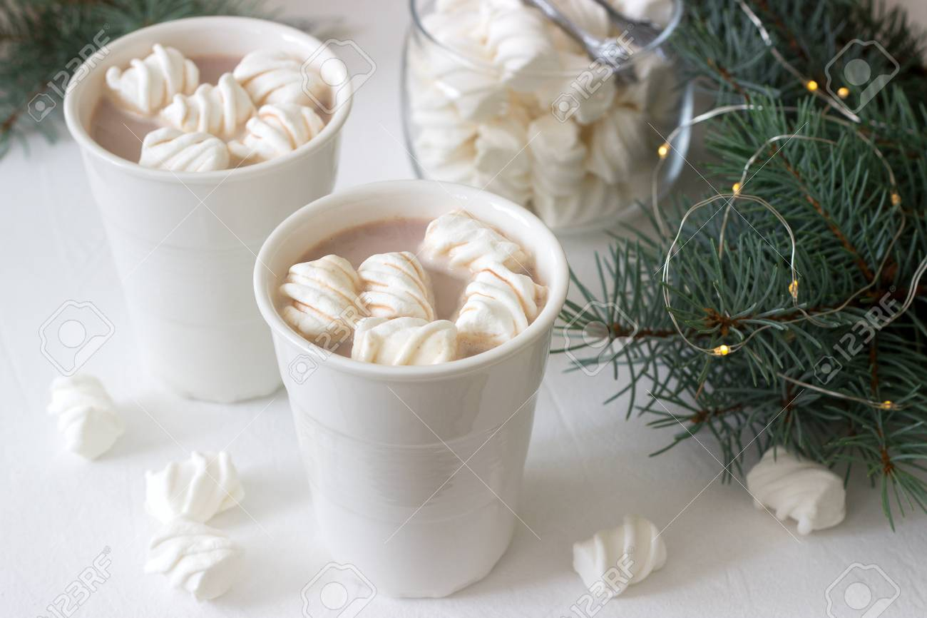 Cocoa with marshmelow in white cups and marshmallows in a glass jar on a white table with spruce branches, a garland and a white star. Selective focus. - 107239882