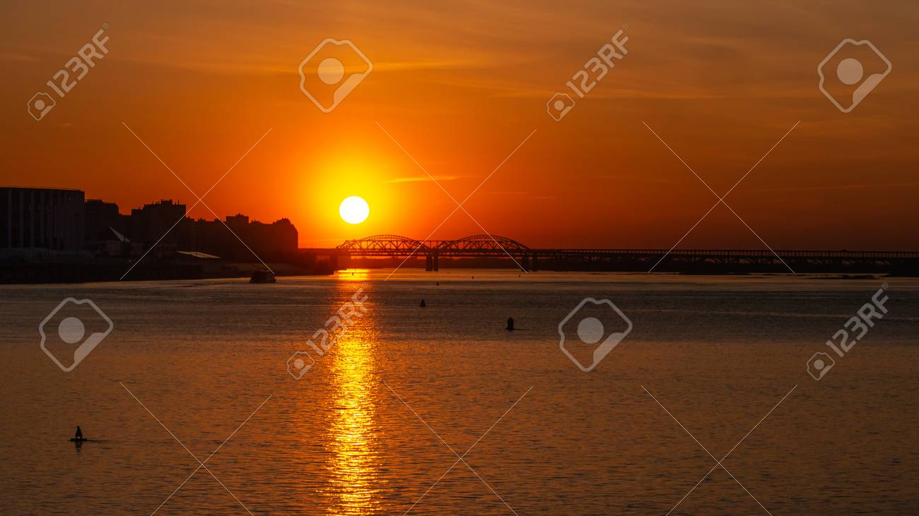 Beautiful sunset over the big river. Big city and bridge on the background. Copyspace for text. - 126753097