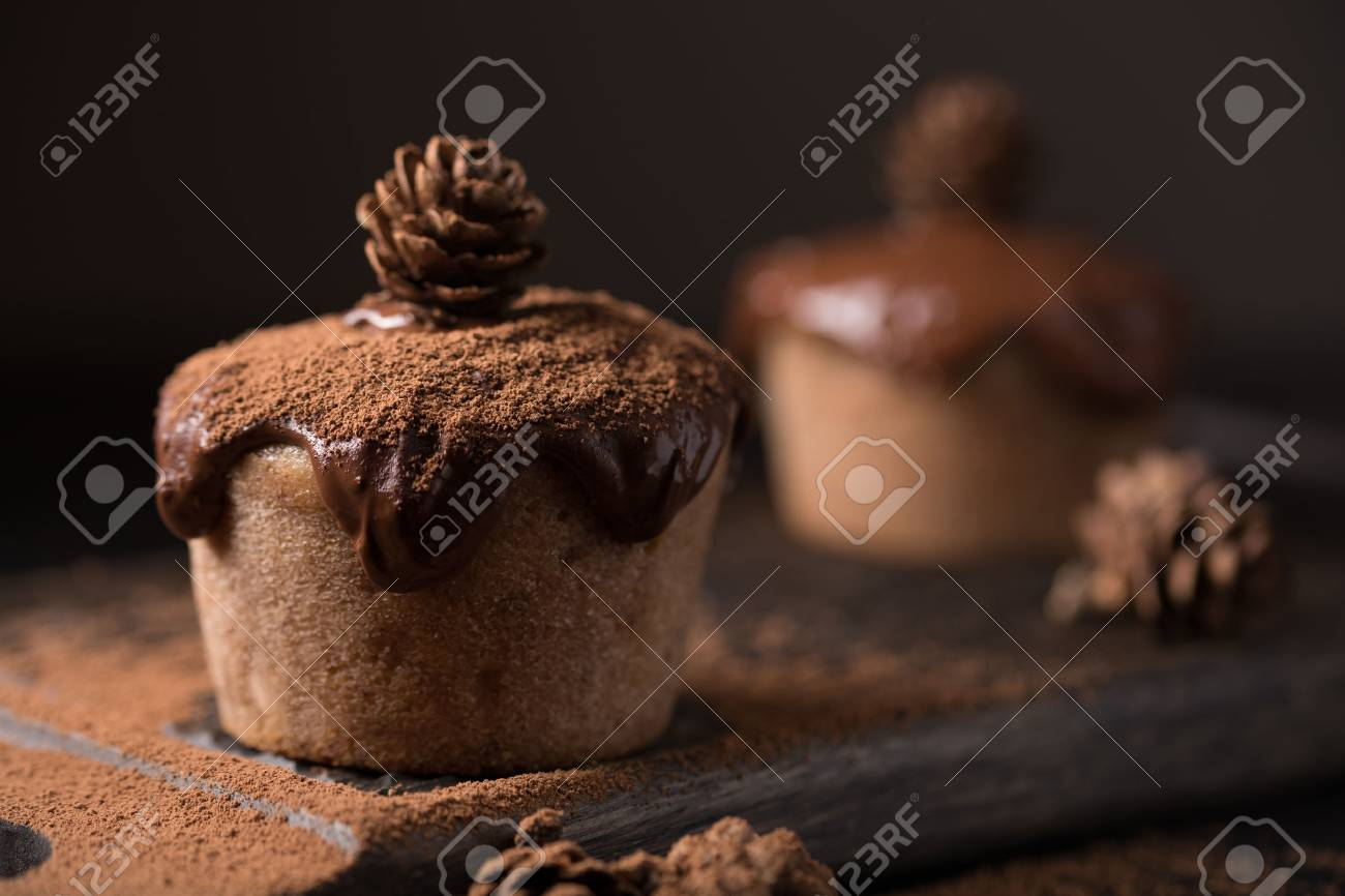 Chocolate muffins, decorated with a small cone on a dark wooden background. Low key. Cupcakes are poured with dark chocolate and cocoa powder. Cupcakes with unusual decoration. - 82112716