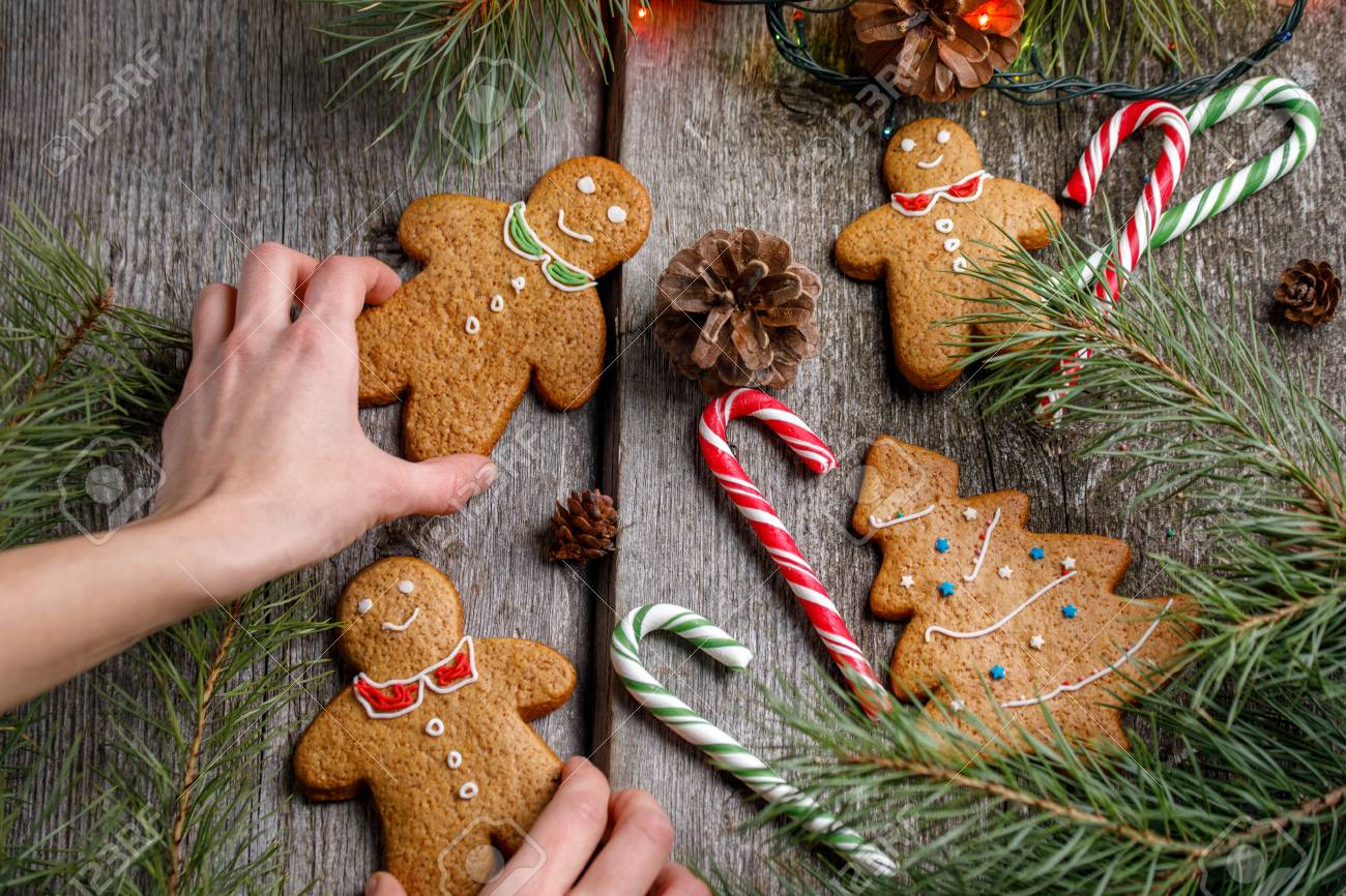 A Girl Is Decorating A Table For Christmas Gingerbread Men