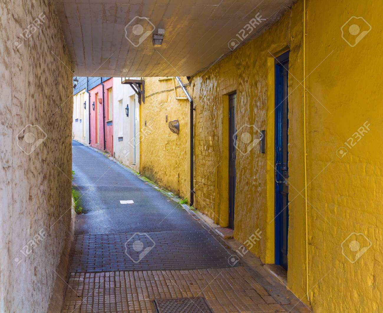 A Small Street With A Tunnel Bright Yellow And Red And White