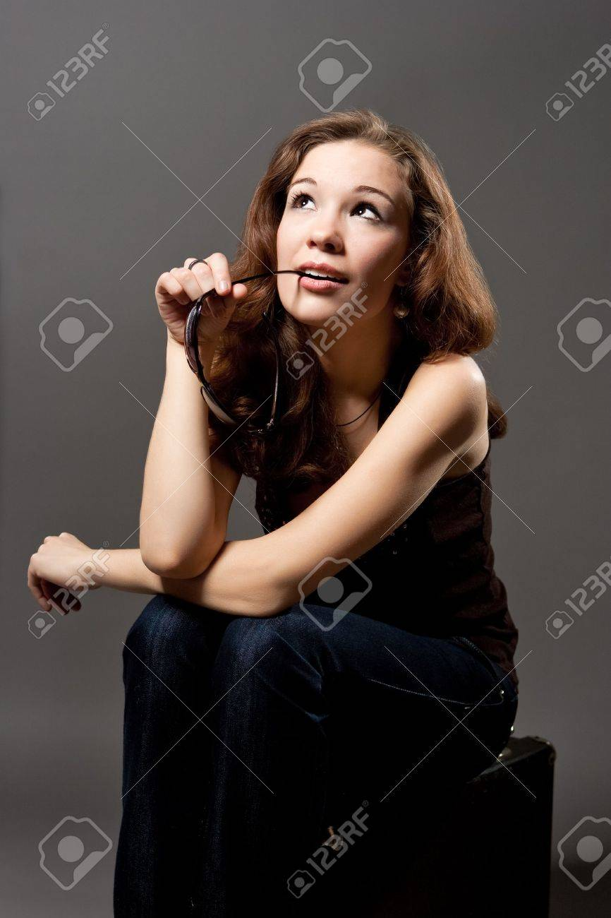 dreaming and relaxing young caucasian girl with sunglasses touching mouth  sitting on suitcase isolated over gray background Stock Photo - 6244364