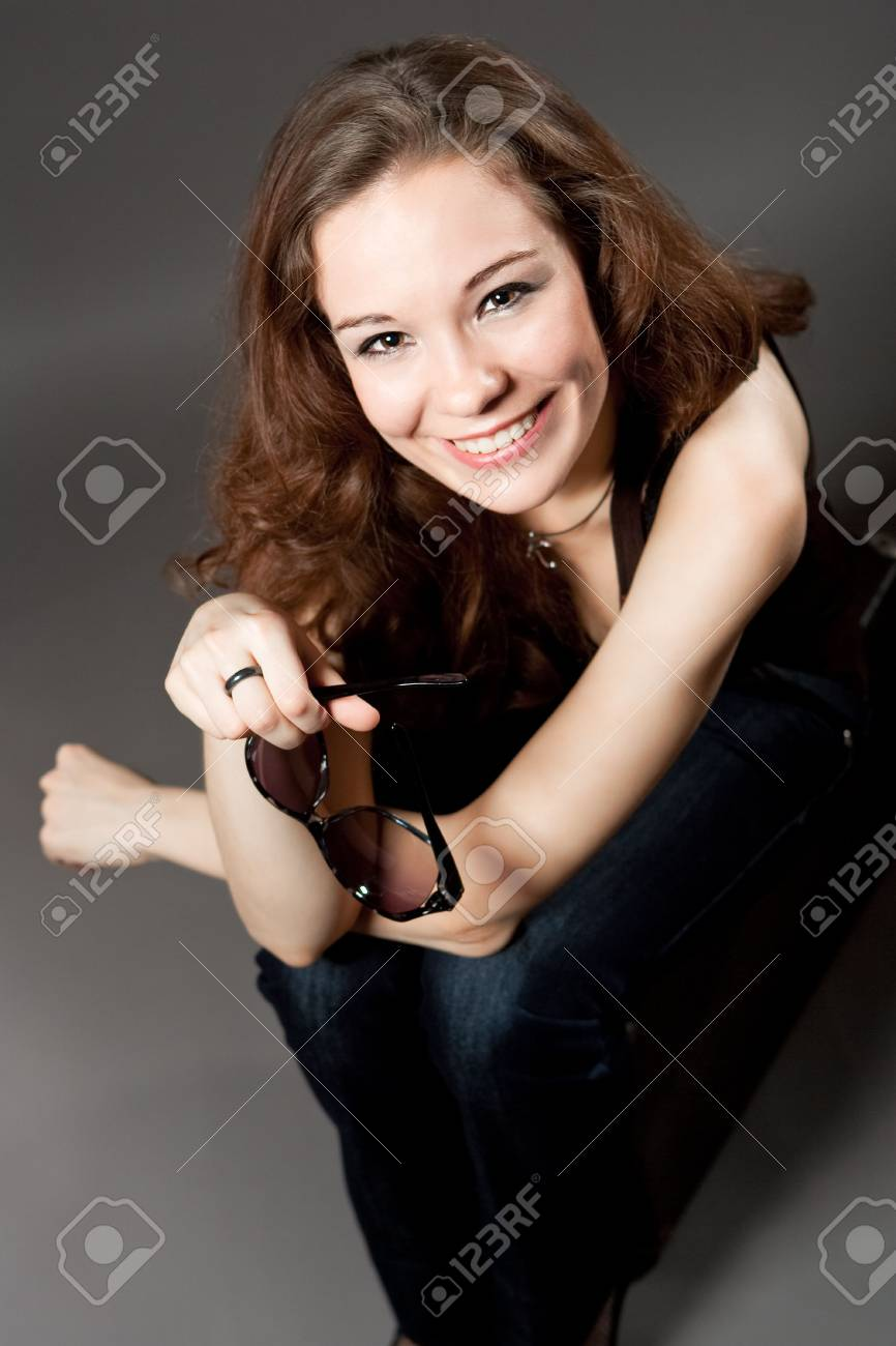 ppy smiling caucasian girl with sunglasses sitting on suitcase isolated over gray Stock Photo - 6244329