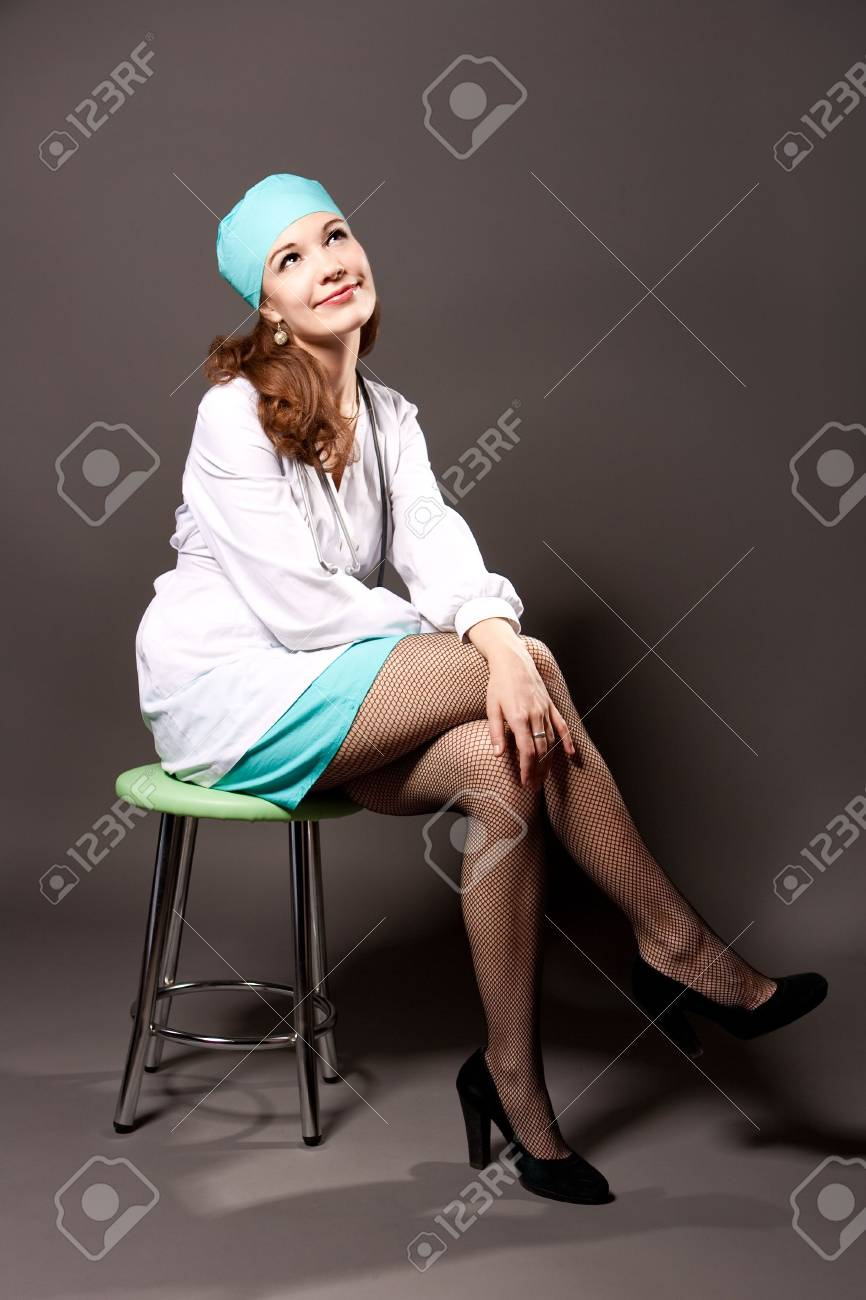 young doctor with whites looking up smiling isolated over gray background Stock Photo - 6244368