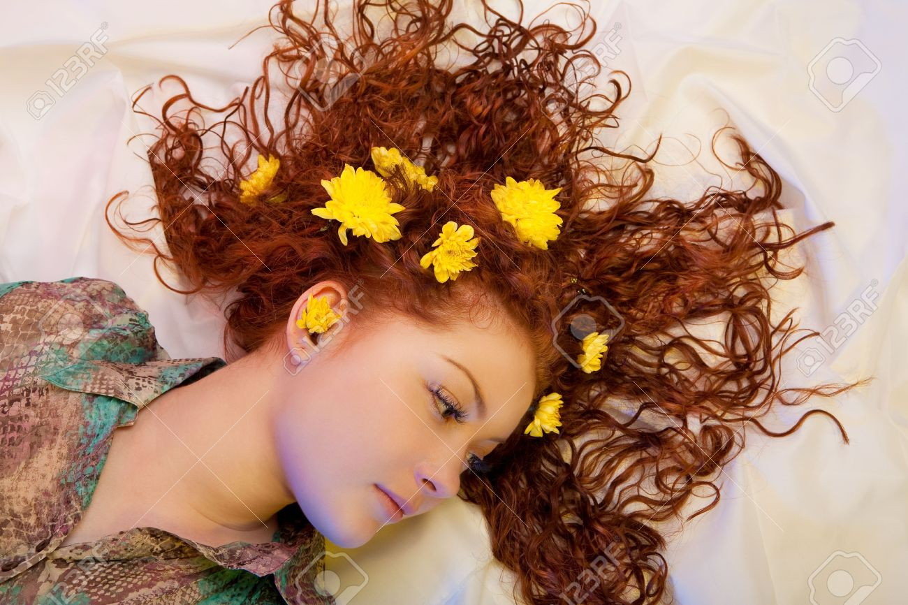 Relaxing Young Caucasian Girl With Flowers In Hair Lying Over