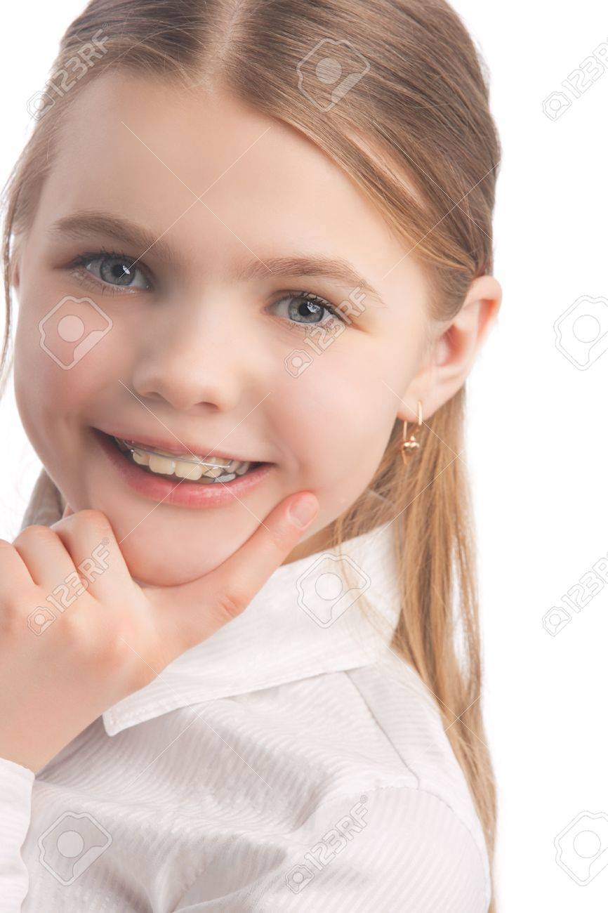 young cute caucasian blond girl wearing teeth braces standing in white shirt isolated over white background smiling Stock Photo - 9981123