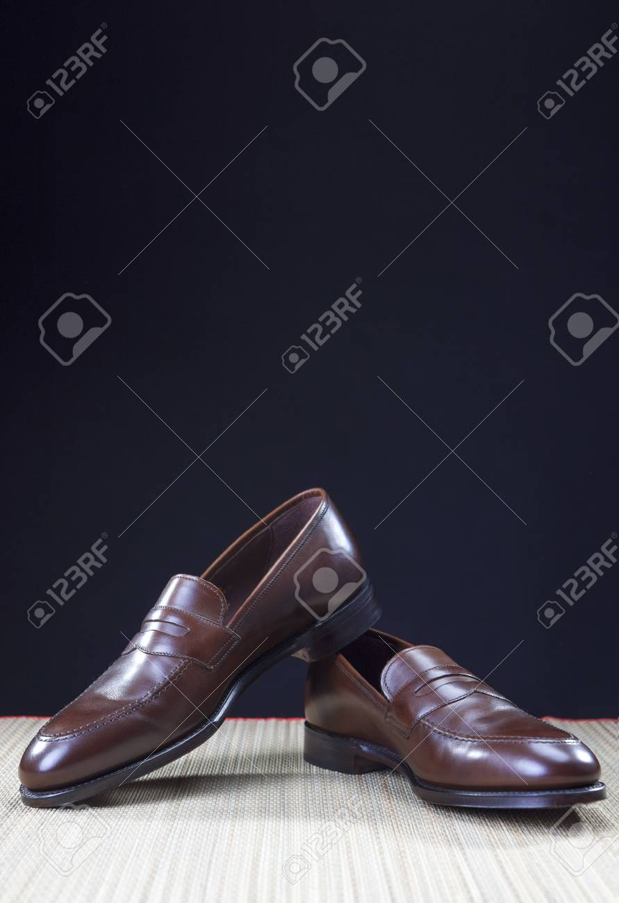 160b2a0f5f1 Shoes concepts. Men s Brown Stylish Penny Loafer Shoes On Straw Surface  Against Black Background.