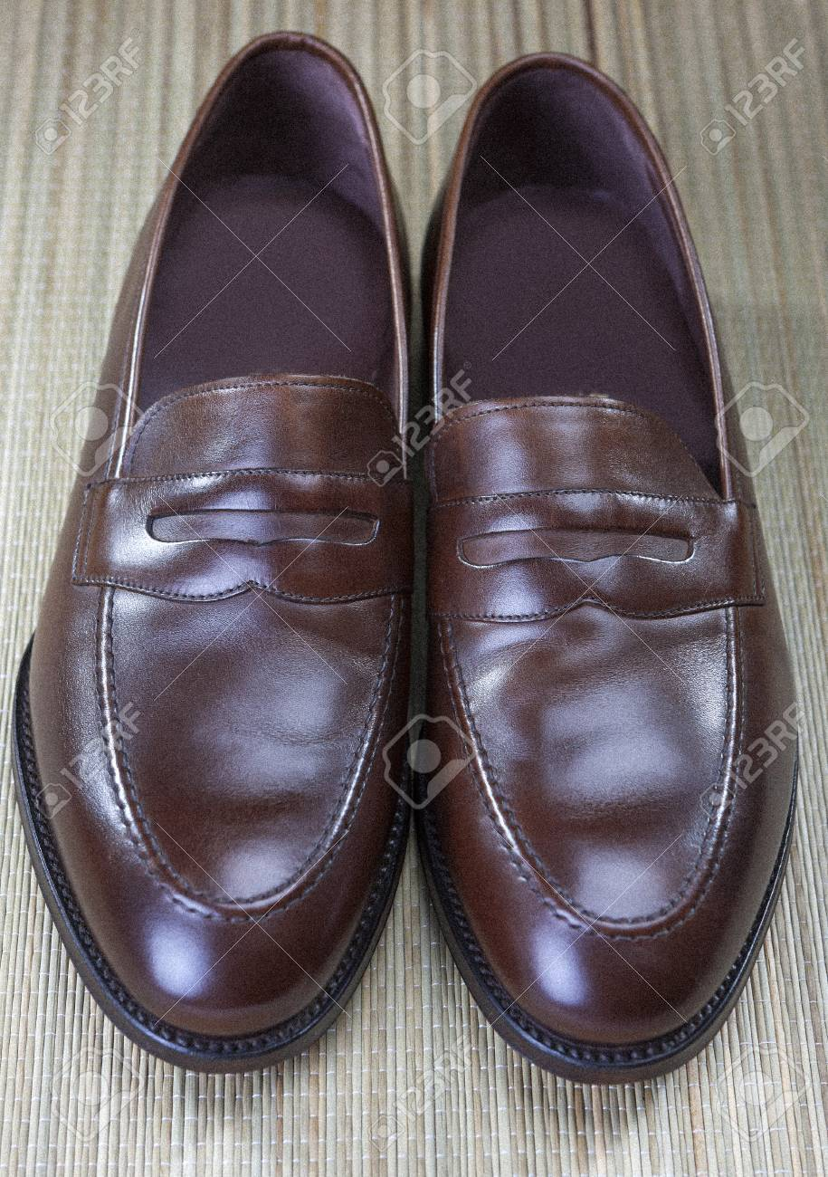 0048758667 Pair of Stylish Expensive Modern Calf Leather Brown Penny Loafers Shoes.Closeup  Shot. Vertical