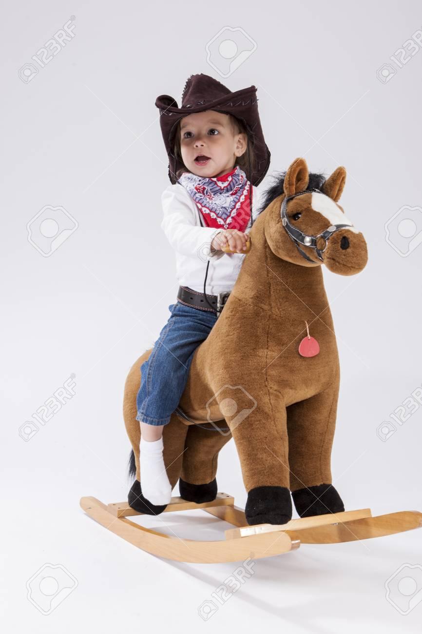 c4abe50e39 Consecuencias para niños pequeños. Sonriendo a feliz niña caucásica en vaquera  ropa posando en caballo