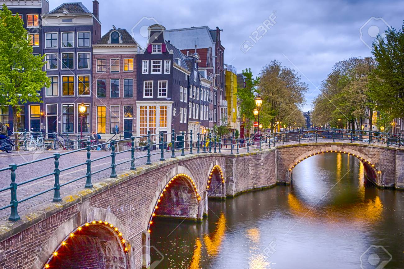 Nighview of Amterdam Cityscape with Its Canals. Illuminated Bridge and Traditional Dutch Houses At Twilight on The Background. Horizontal Shot - 102817248