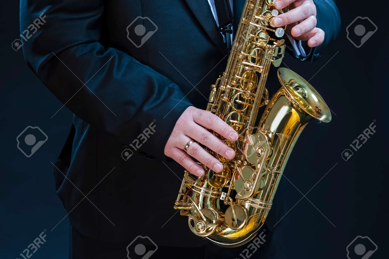 Closeup of hands of Professional Saxophonist Player Against Black. Horizontal image Orientation - 147435903