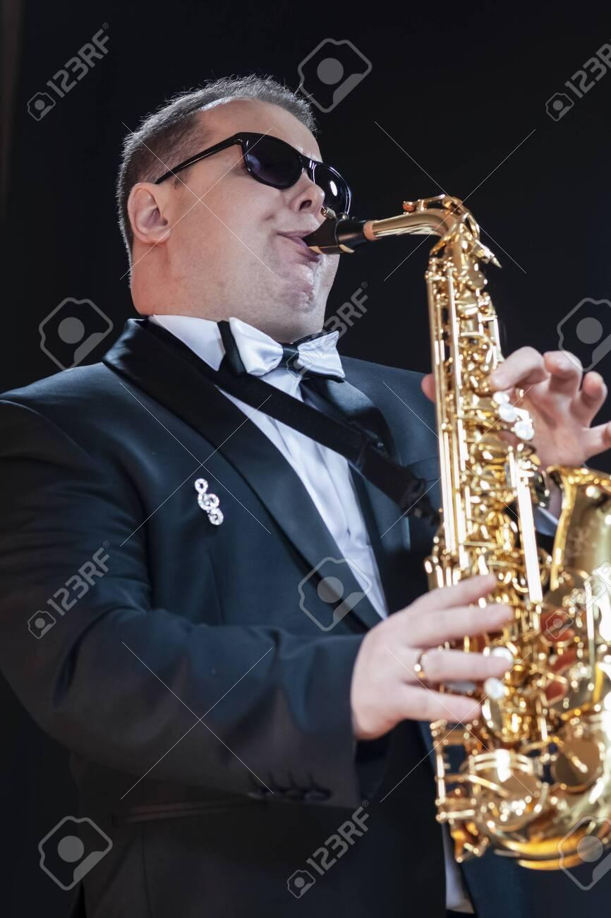 Portrait of Passionate and Extravagant Caucasian Saxophonist in Dark Suit Posing in Sunglasses Against Black. Vertical Image - 149772887