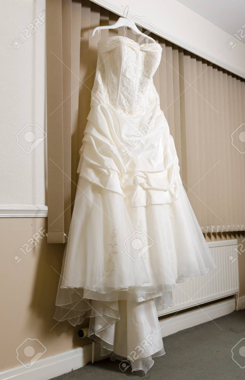 A Beautiful Cream And Clean Wedding Dress Hanging In Front Of ...