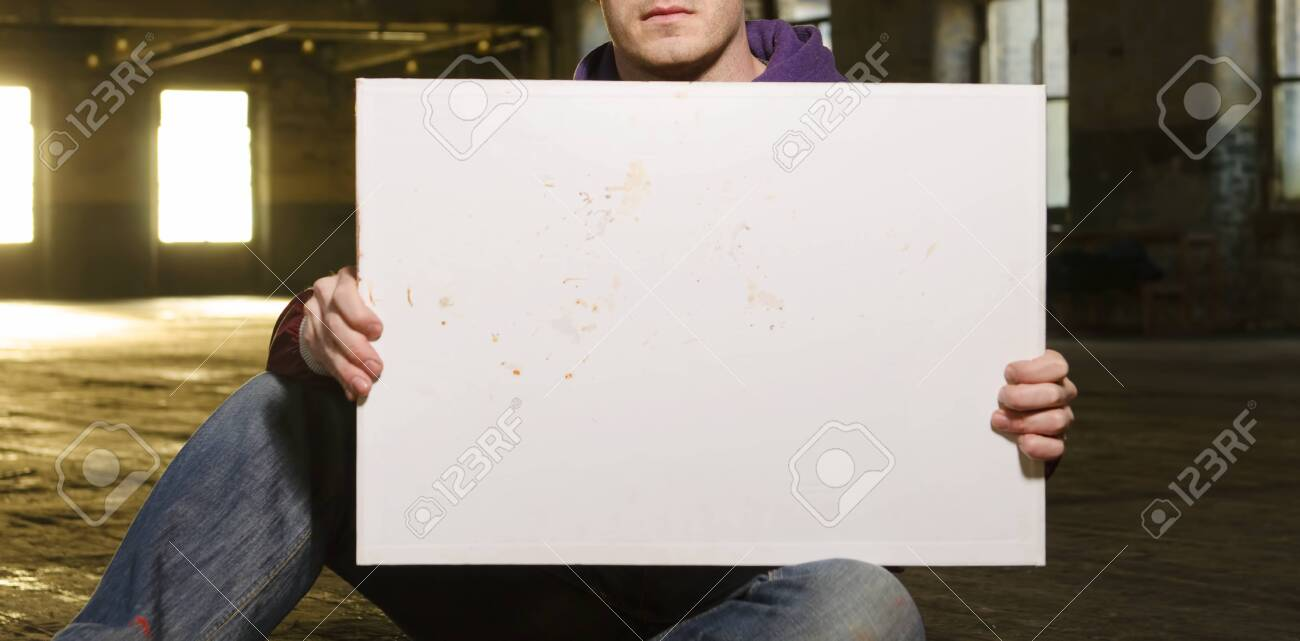 A white male holding an empty blank protest billboard in an urban warehouse setting. People power, power to the people. blank mock board for compositing. - 144428496