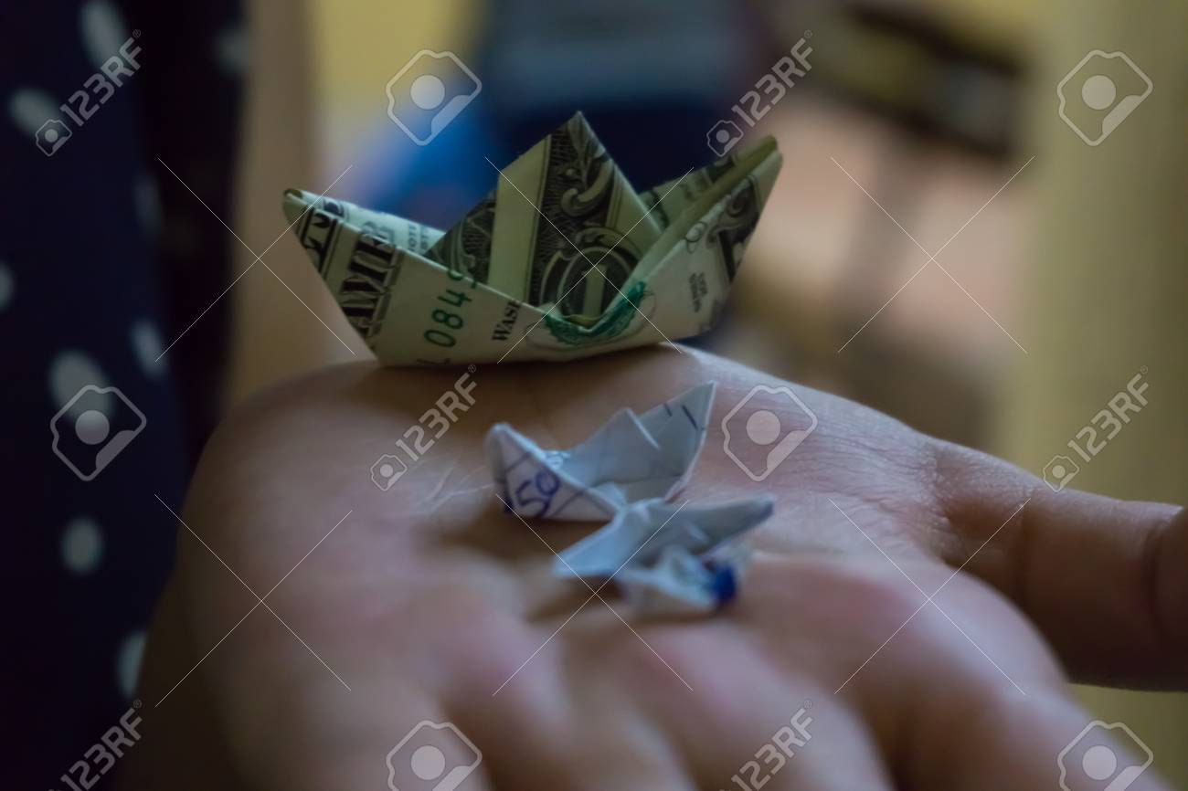 Stock P O Three Paper Boats And A Boat Made With A Dollar Bill On One Hand