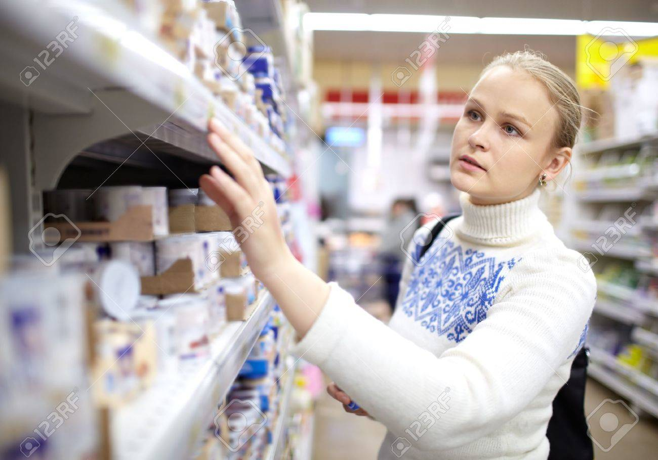 Young woman is choosing food for her child in the supermarket Stock Photo - 15678762