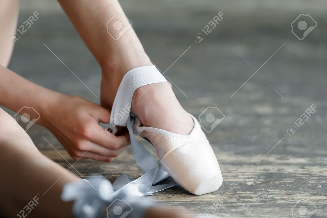 close-up shot of a ballerina taking off the ballet shoes sitting