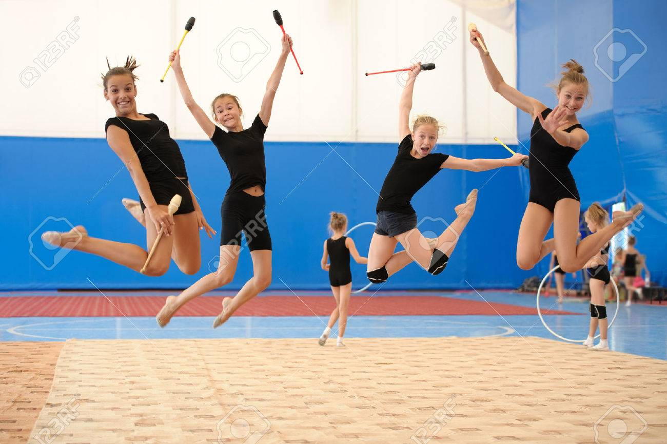 Group of four young female gymnasts posing with Indian clubs in a high jump - 32828165