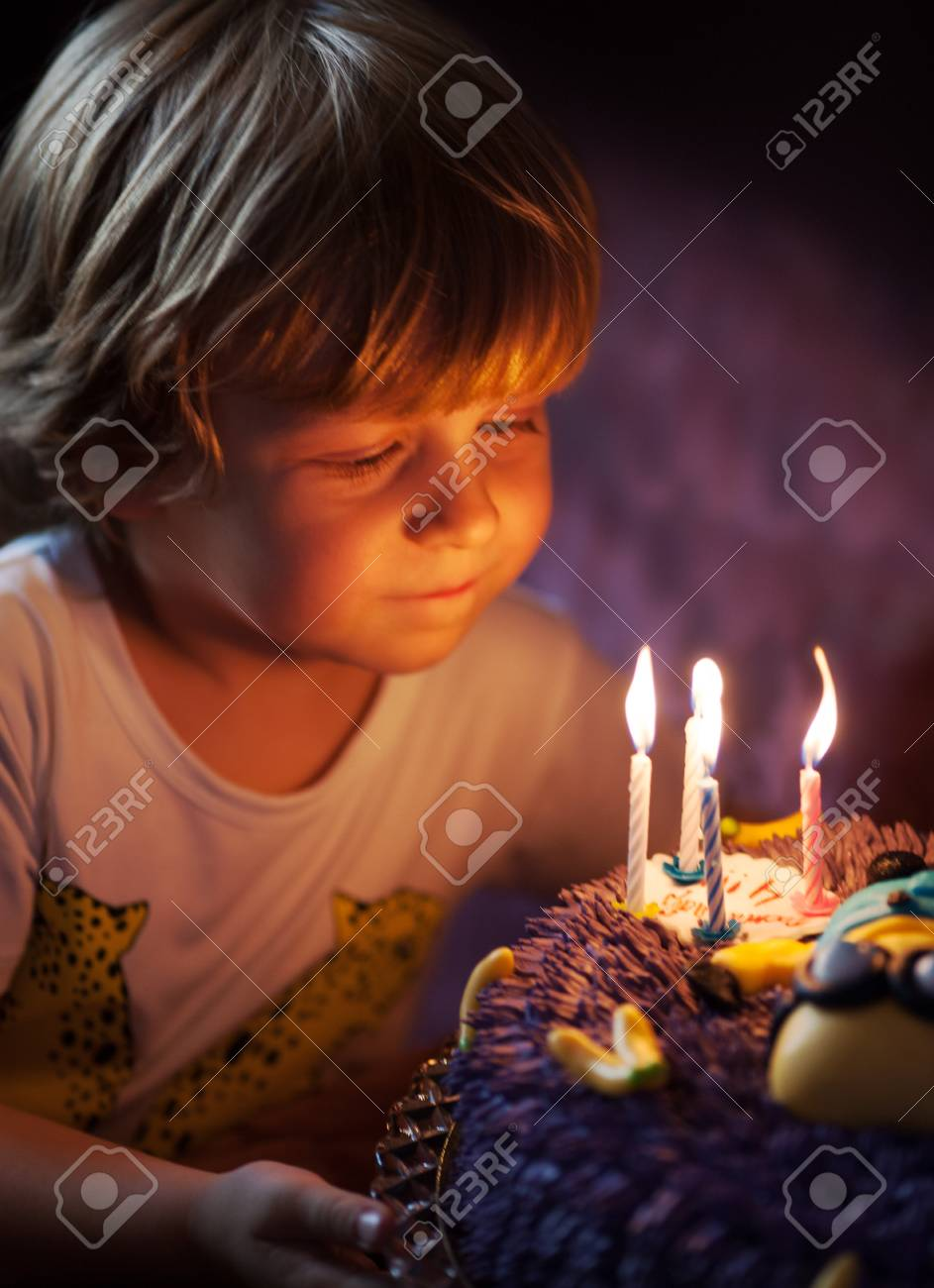 Little Boy Blows Out Candles In The Cake For His 4th Birthday Stock Photo