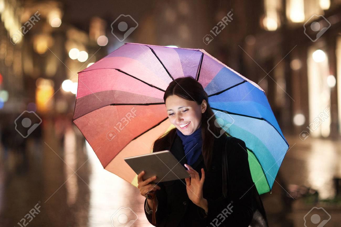banque dimages bonne jeune fille avec un parapluie color en utilisant lordinateur tablette en plein air elle debout dans la rue de la ville dans la - Parapluie Color