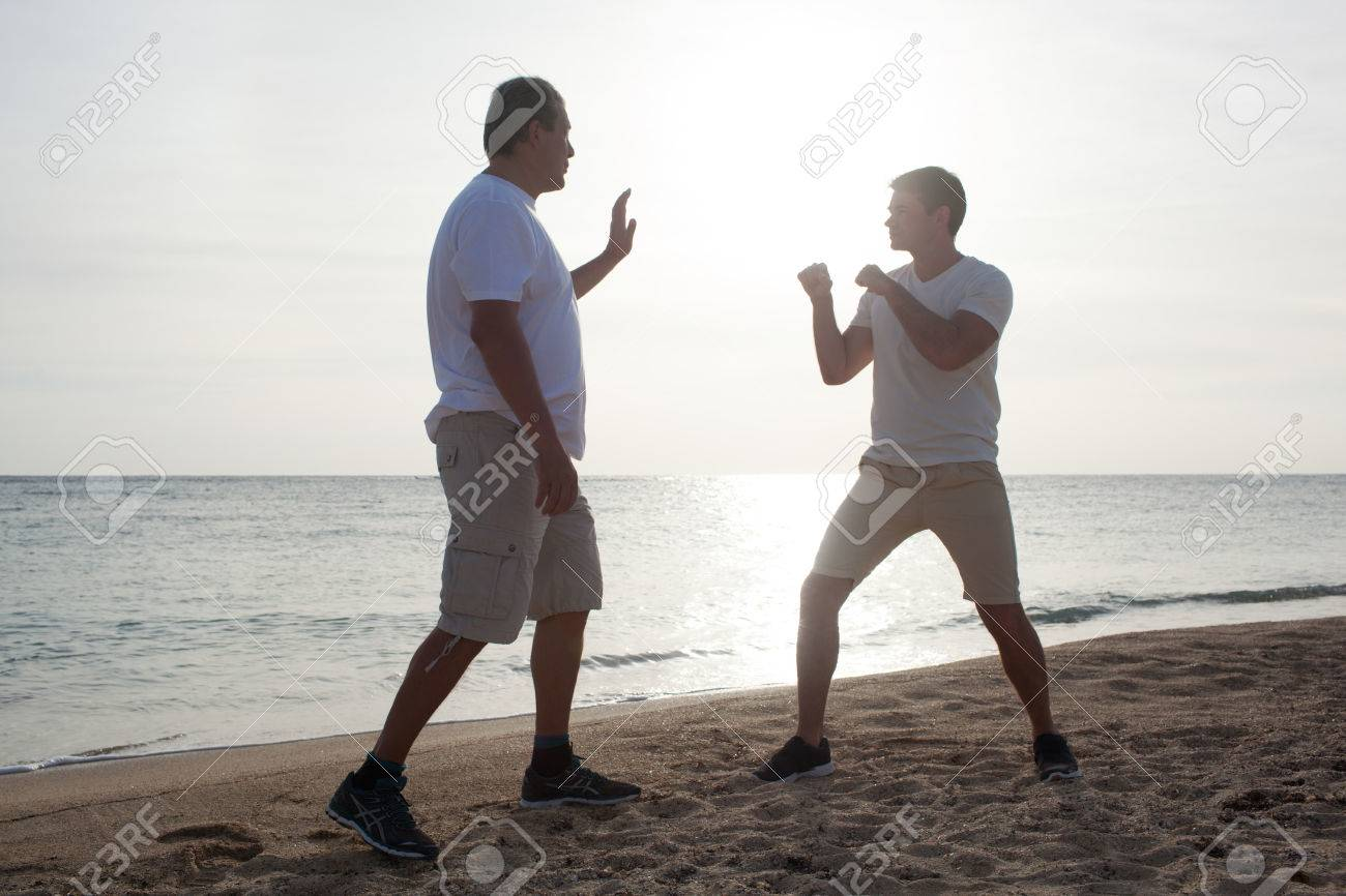 Stock Photo - Young and mature men on the beach on a bright sunny day. They  have open-air boxing training