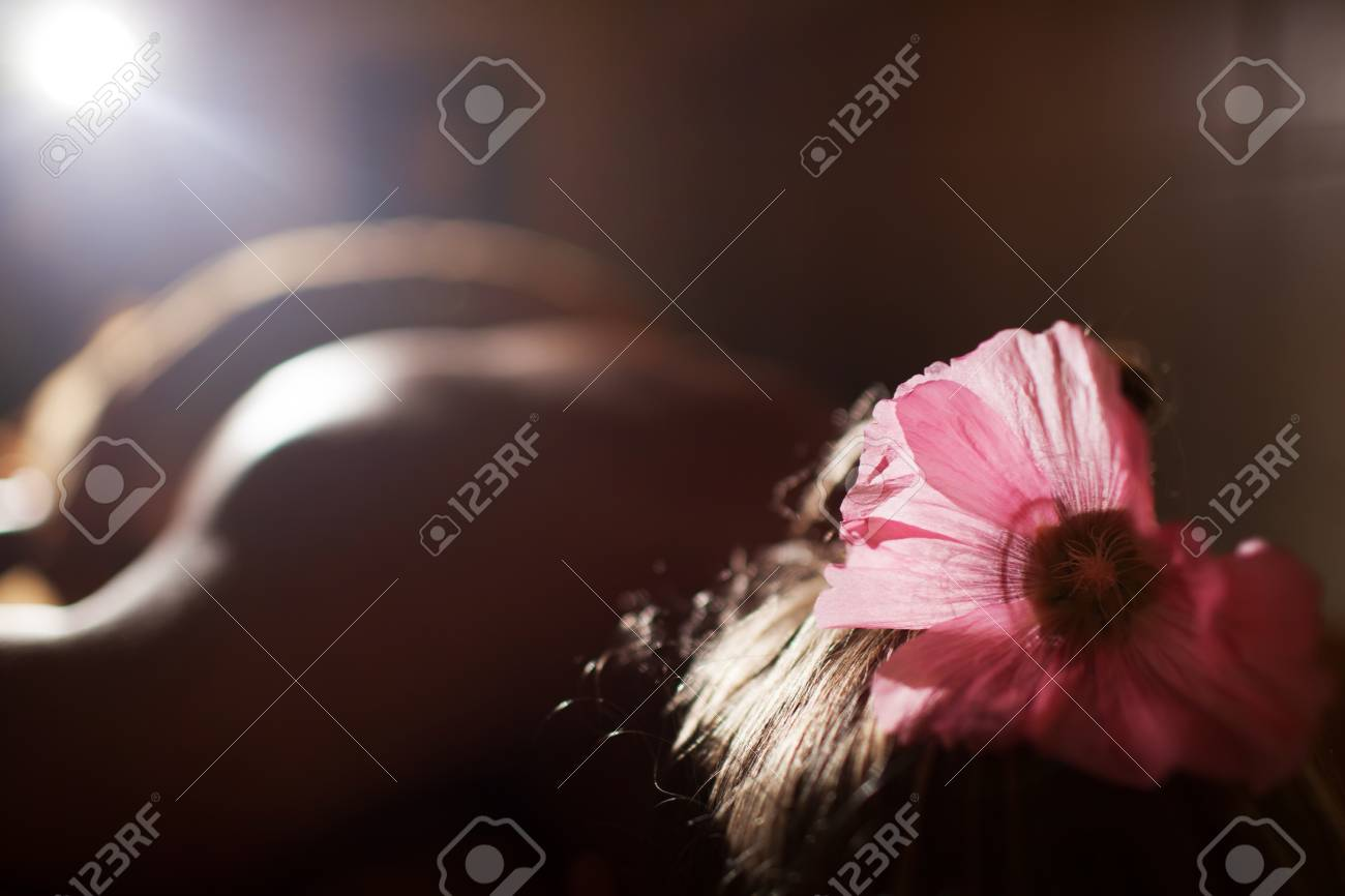 Relaxed Woman With Pink Flower In Hair Lying At Beauty Spa Salon