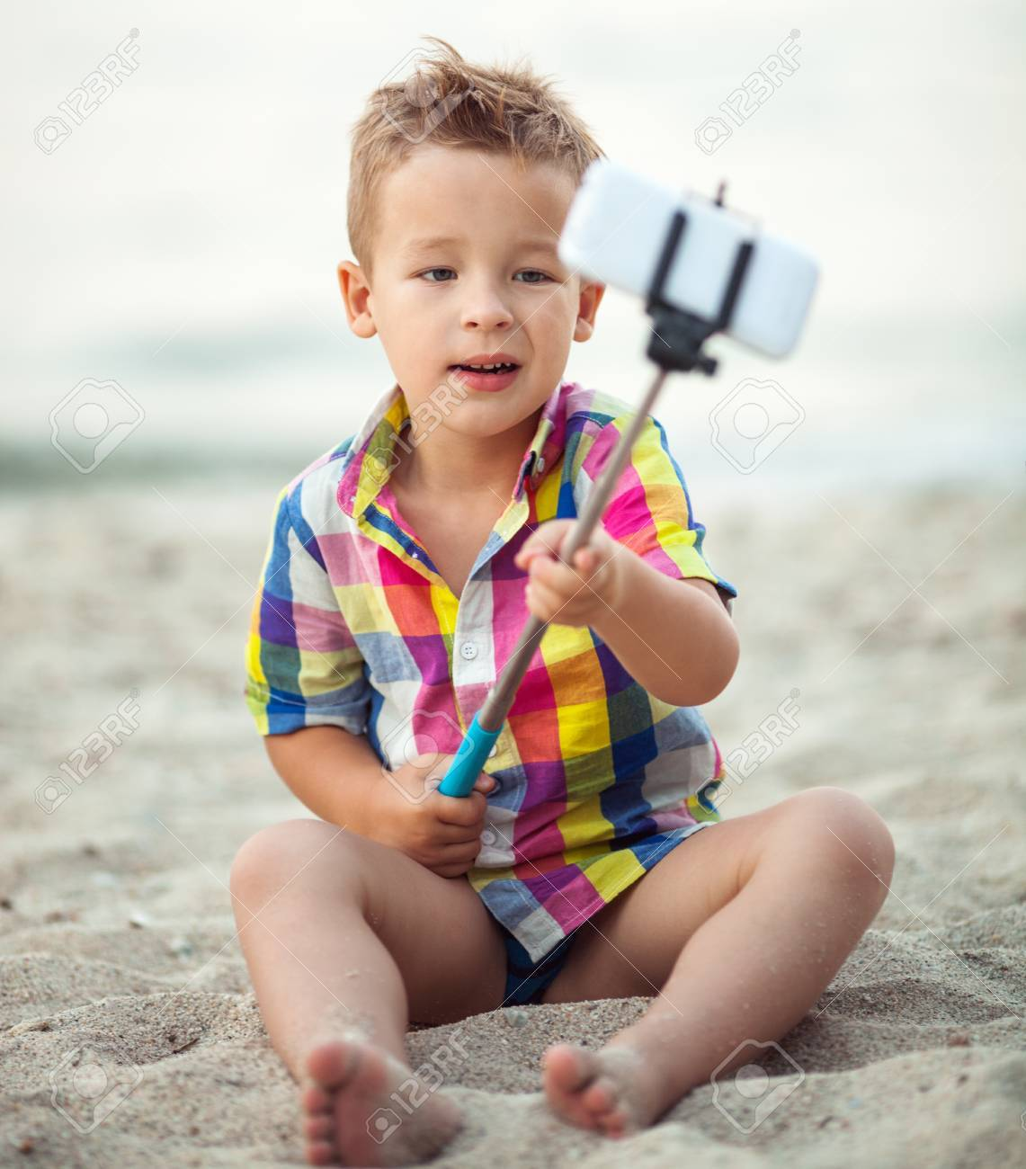 f7c85a3e1 Cute little boy in colorful checkered shirt sitting on the sand and taking  picture with smart