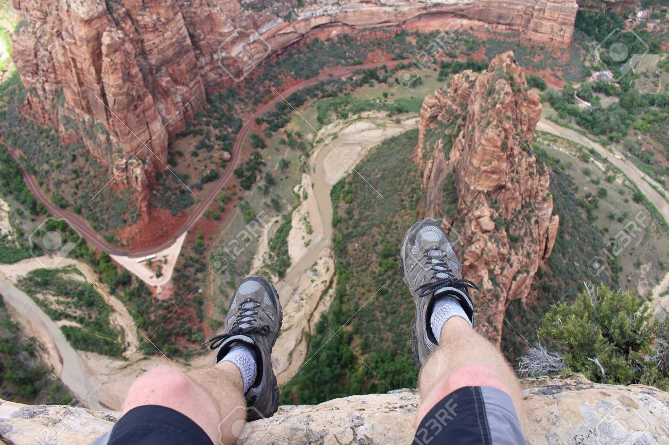 First person perspective shot from a hiker sitting at the edge of a cliff at Angel's Landing in Zion National Park. - 70868462