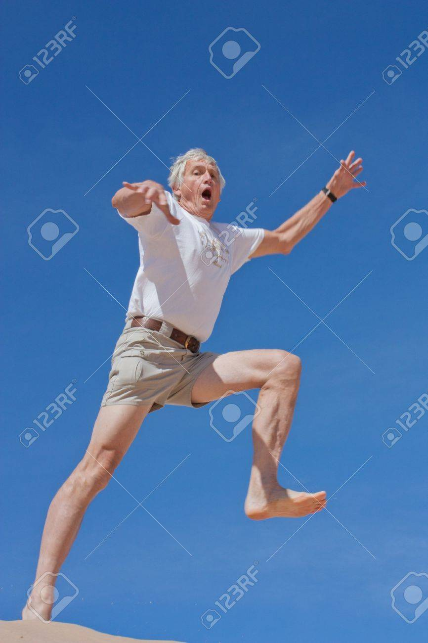 A mature male in his 60s takes a fearful leap into the blue yonder - 12778786