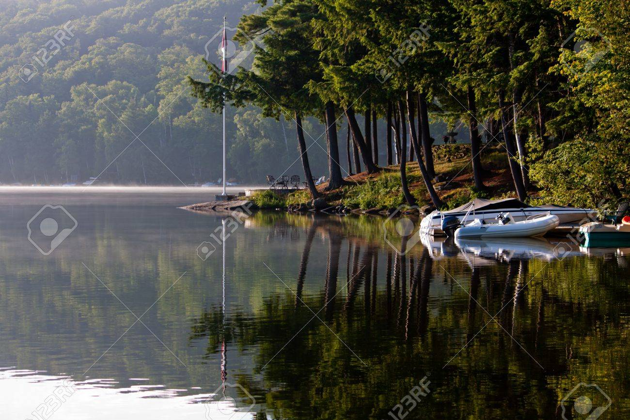 Morning breaks over the glassy still lake, looking out at boats docked and Muskoka pine trees - 18127063