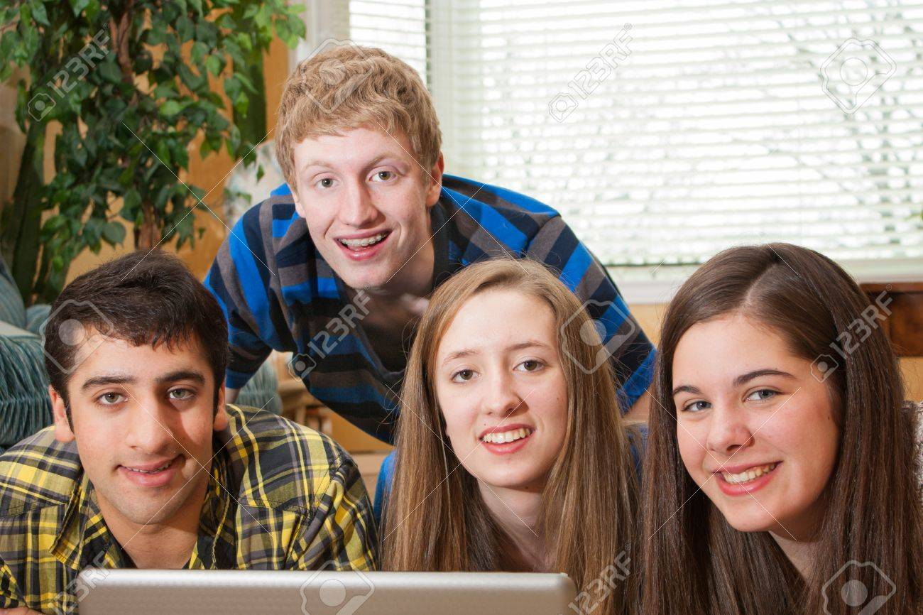 A diverse group of teenagers gathered around a laptop in a home setting looking at the camera - 18691533