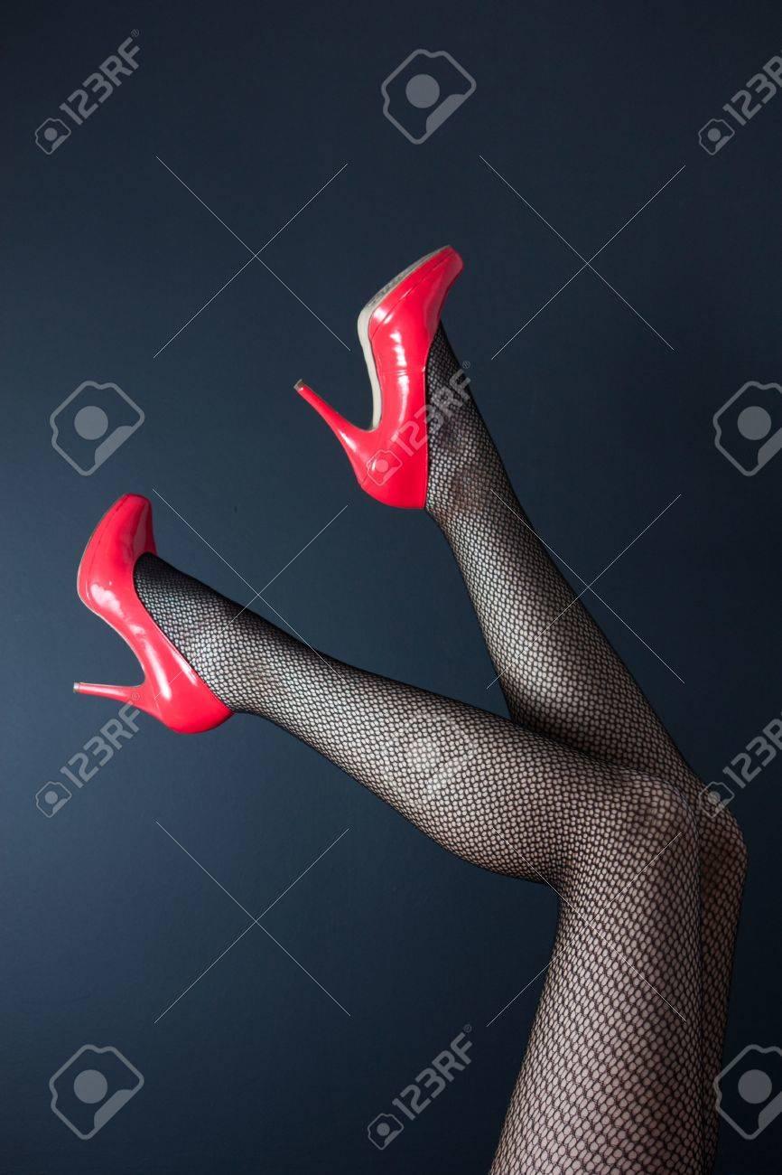 06dbb1d90 Un par de bien torneadas piernas femeninas en medias de red con brillantes  zapatos rojos de tacón alto en un fondo oscuro
