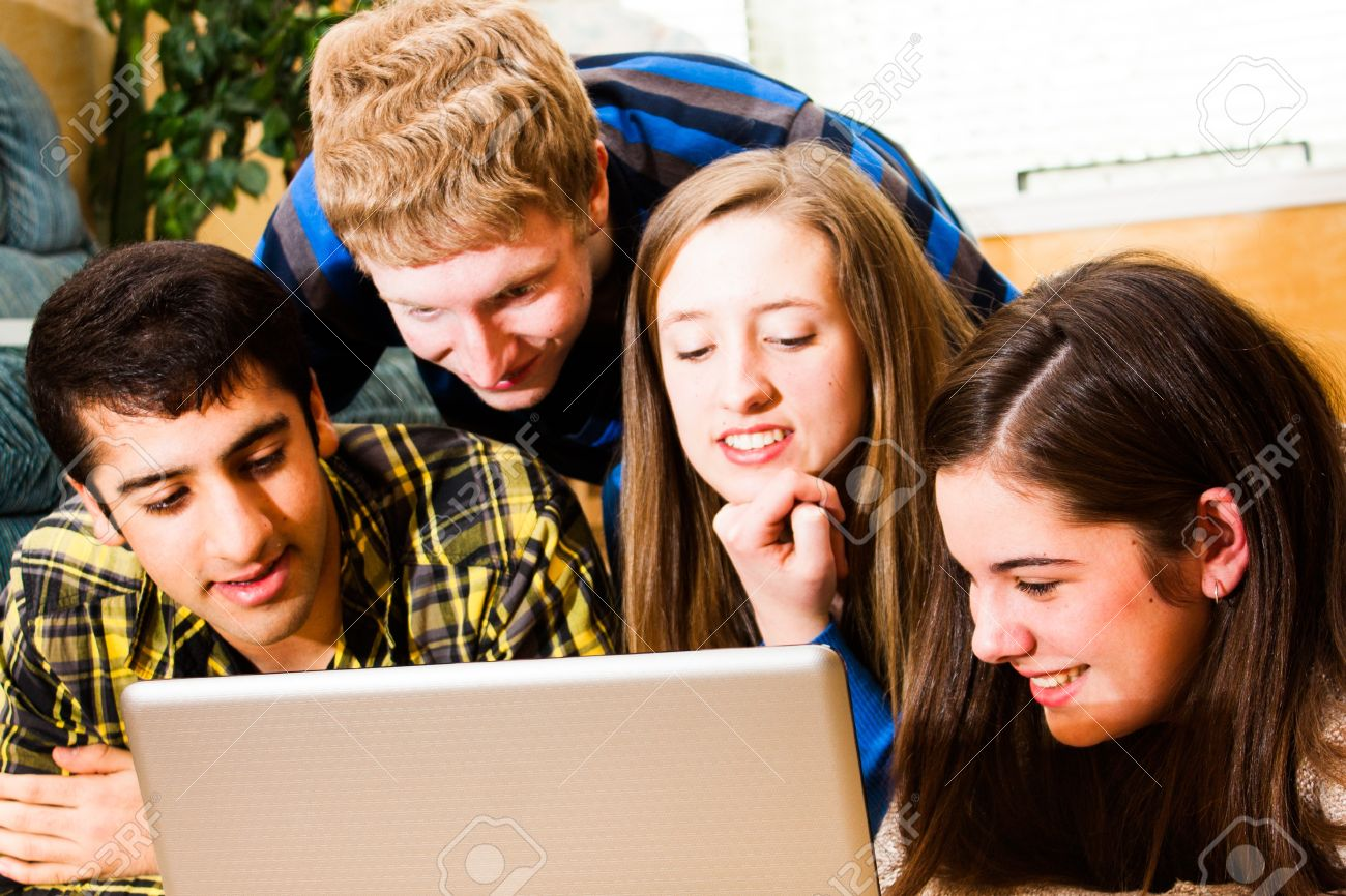 a group of teens viewing a computer screen together High saturation - 19293128