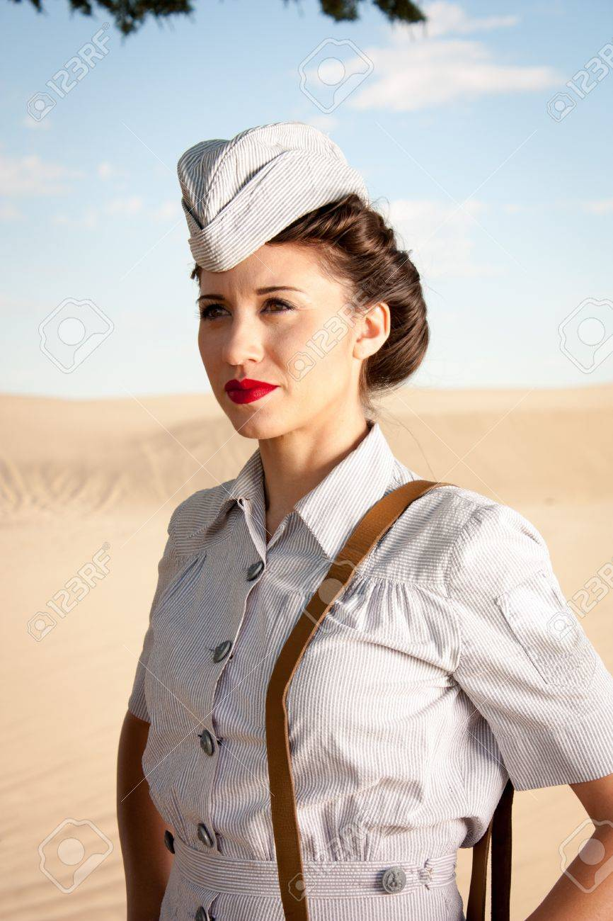 A beautiful young WWII nurse, in authentic uniform, stares off into the dry dusty landscape close up head and shoulders - 21438418