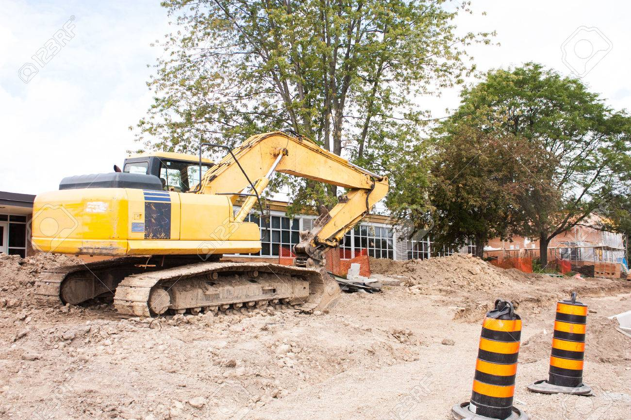A local school site under renovation. An excavator clears the area in the front with the school building in the background - 23014555