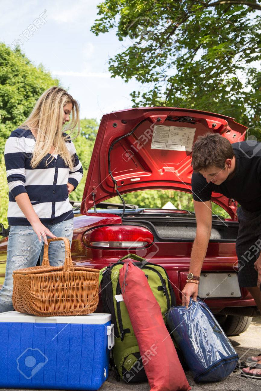 A young couple packs their trunk for a camping trip - 30121138